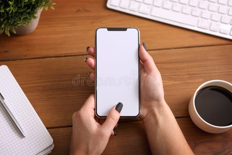 Weibliche Hände, die intelligentes Telefon mit weißem leerem leerem Schirm auf brauner Schreibtischtabelle halten stockbild