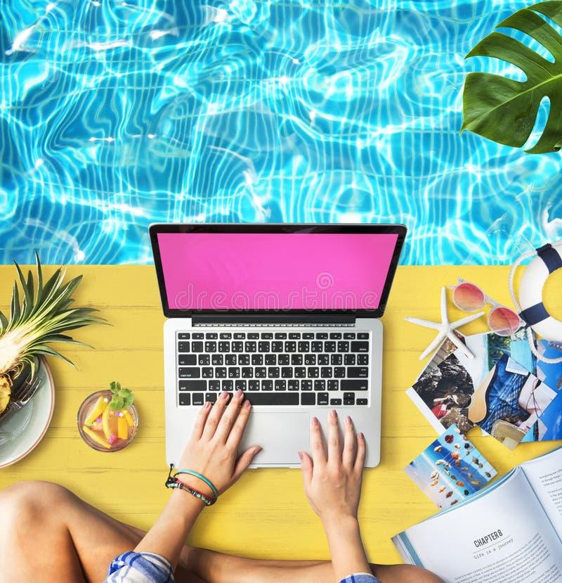 Weibliche Hände, die Macbook-Poolside-Konzept schreiben stockfotografie
