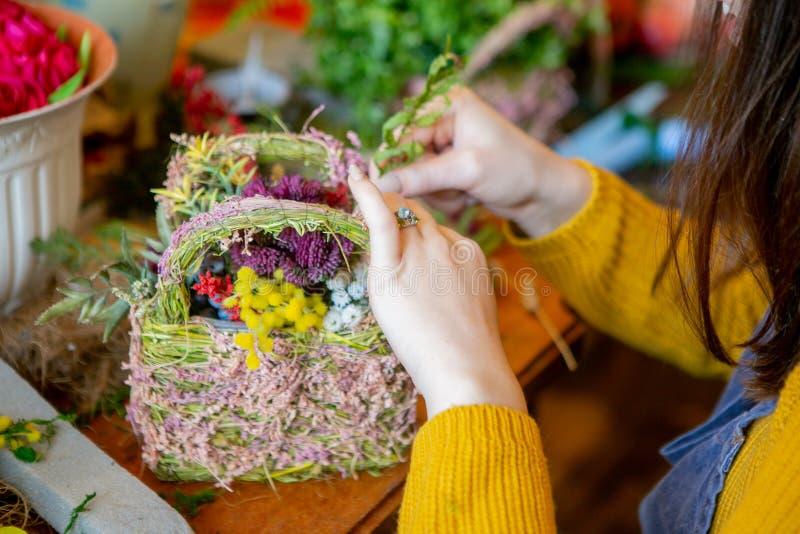 Weibliche Hände, die schönen Blumenstrauß von den Blumen auf Hintergrund machen lizenzfreie stockfotos