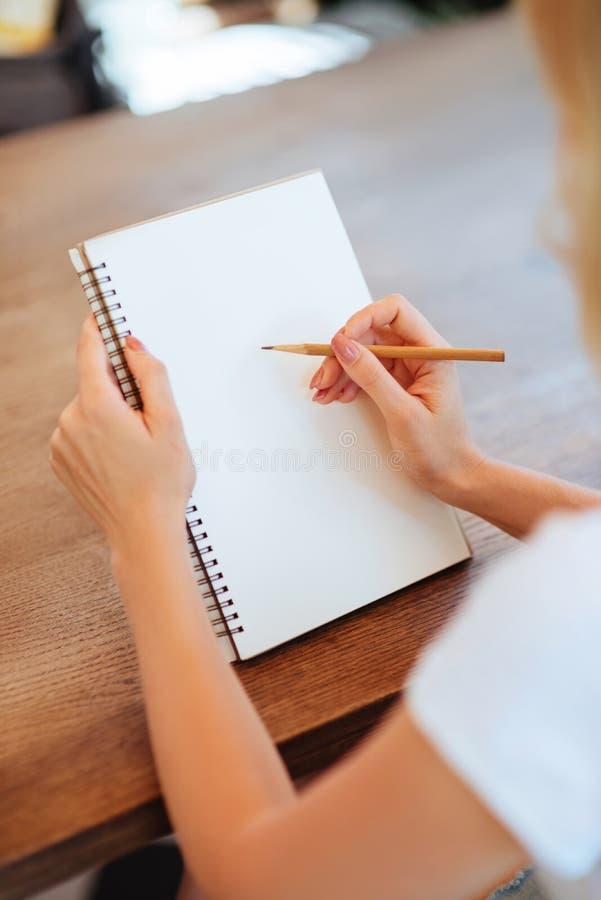 Weibliche Hände, die Schafe im Notizbuch zeichnen stockfotografie