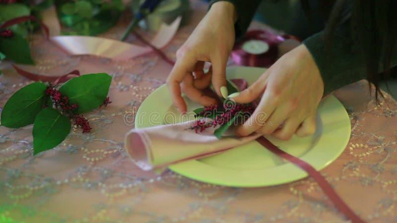 Weibliche Hände, die Servietten falten faltende Serviette des Kellners künstlerisch mit Blumen am Restauranttisch stock video footage