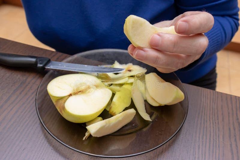 Weibliche Hände, die weg Haut eines gelben Apfels mit einem Messer abziehen stockfoto