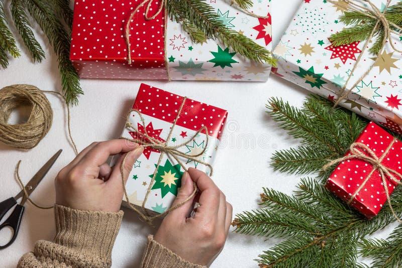 Weibliche Hände, die Weihnachtsgeschenkbox einwickeln stockfotografie
