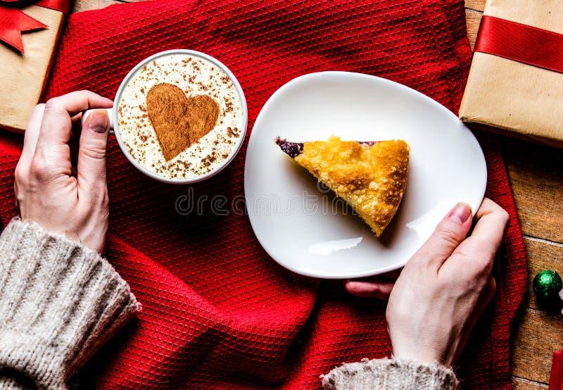 Weibliche Hände, die Weihnachtstorte und -Tasse Kaffee halten stockfoto