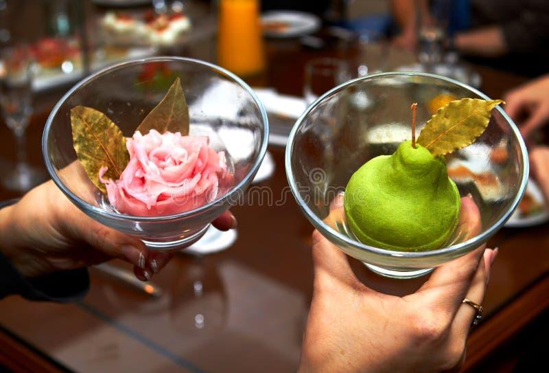 Weibliche Hände, die zwei Vasen mit birnenförmiger Eiscreme halten stockfoto