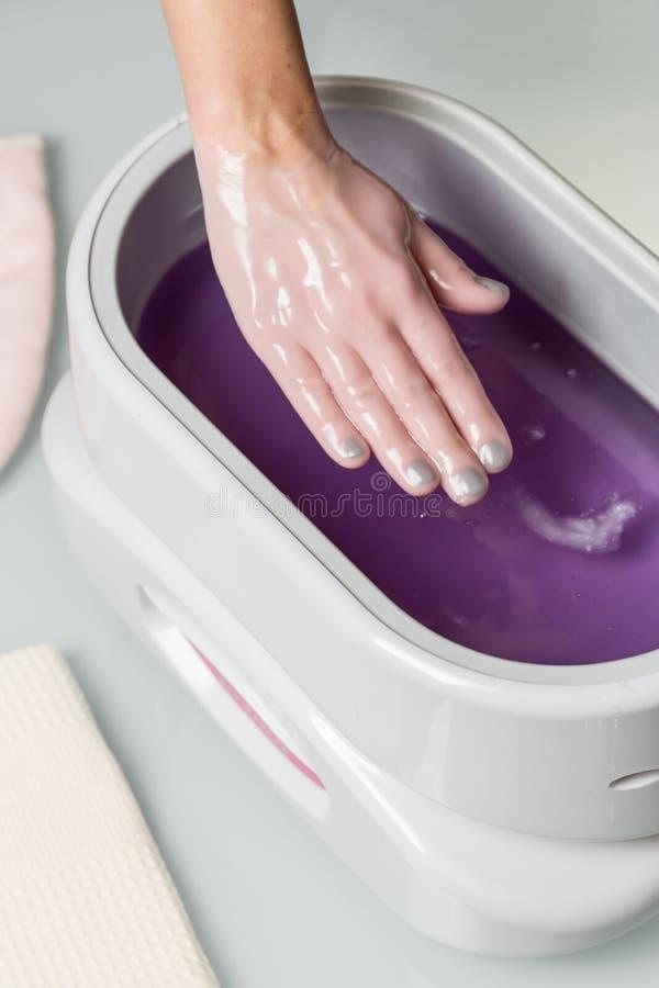 Weibliche Hände in einer Paraffinwachsschüssel lizenzfreie stockfotos