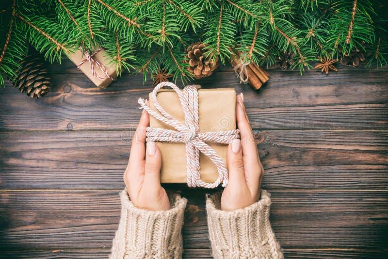 Weibliche Hände halten die Verpackung der Weihnachtsgeschenkbox mit rosa Band auf dunklem Holztisch Beschneidungspfad eingeschlos lizenzfreie stockbilder