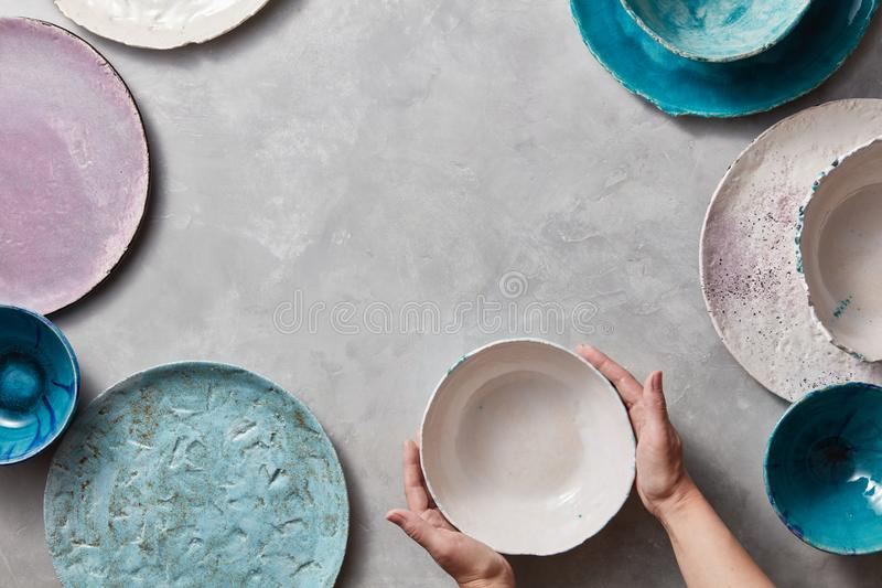 Weibliche Hände halten eine weiße keramische Schüssel auf einer grauen Marmortabelle Lehm handcraft Schüsseln, Platten von versch stockfotografie