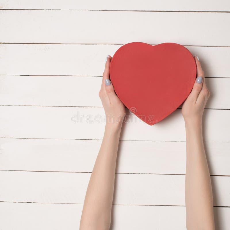 Weibliche Hände halten einen geformten Kasten des roten Herzens vor dem hintergrund eines weißen Holztischs stockfotos