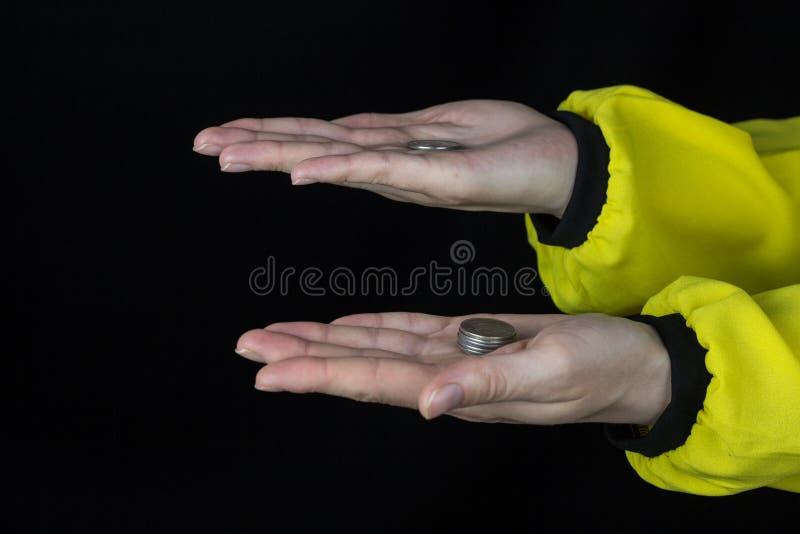 Weibliche Hände halten Münzen in zwei Palmen, schwarzer Hintergrund lizenzfreie stockfotos