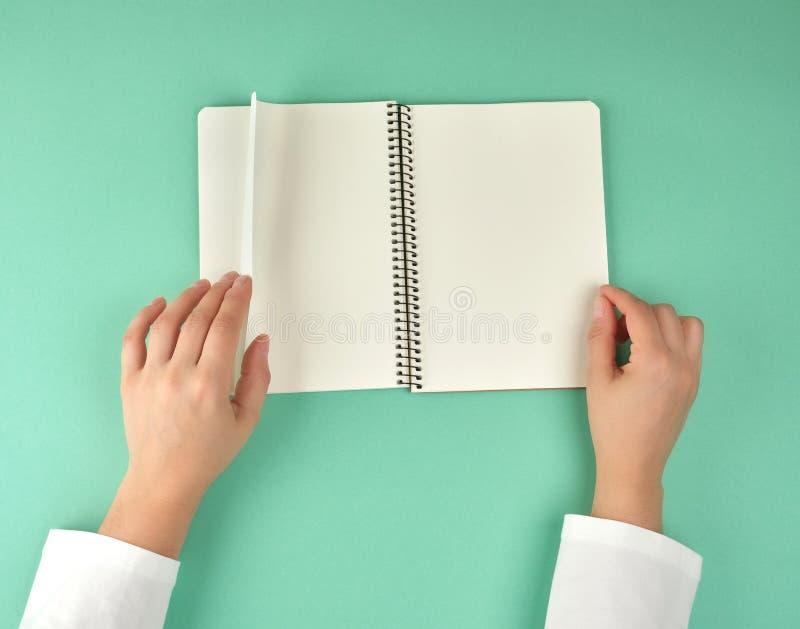 weibliche Hände halten offenes gewundenes Notizbuch mit sauberen weißen Blättern lizenzfreie stockfotografie
