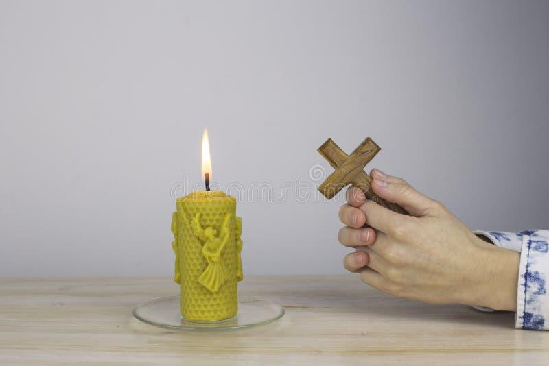 Weibliche Hände im Gebet halten ein Kreuz stockfoto