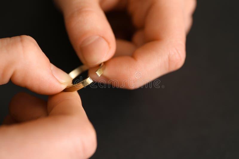 Weibliche Hände mit defektem Ring auf dunklem Hintergrund, Nahaufnahme Konzept der Scheidung lizenzfreie stockfotografie
