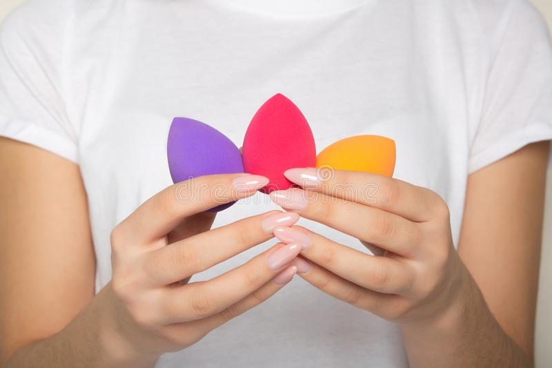 Weibliche Hände mit der schönen Maniküre halten purpurrot, Rosa und orange Schönheitsmischmaschinen stockfotos