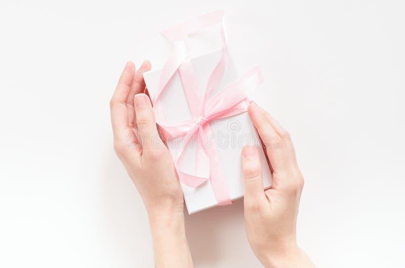 Weibliche Hände mit einer Geschenkbox mit einem rosa Band Konzeptfeiertag, Geschenk, Glückwünsche Draufsicht, flache Lage stockbild