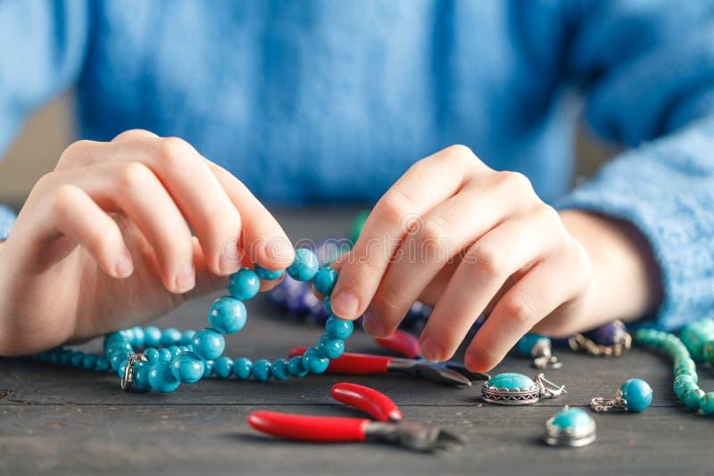 Weibliche Hände mit farbiger Perlenhalskettenherstellung stockbilder