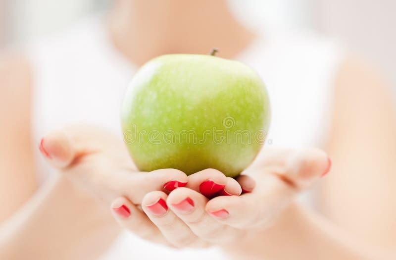 Weibliche Hände mit grünem Apfel lizenzfreie stockfotografie