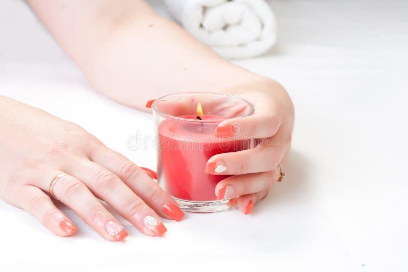 Weibliche Hände mit Kerzen- und Nagelkunst lizenzfreie stockbilder