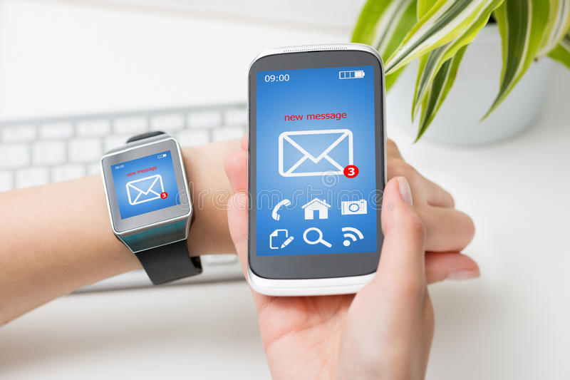 Weibliche Hände mit smartwatch und Telefon mit E-Mail stockbild