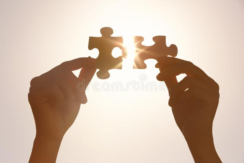 Weibliche Hände mit Stücken des Puzzlespiels und der scheinenden Sonne auf Hintergrund lizenzfreie stockfotografie