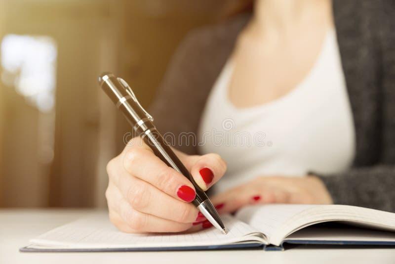 Weibliche Hände mit Stiftschreiben auf Notizbuch Tagebuch, Pläne, Journalist lizenzfreies stockfoto