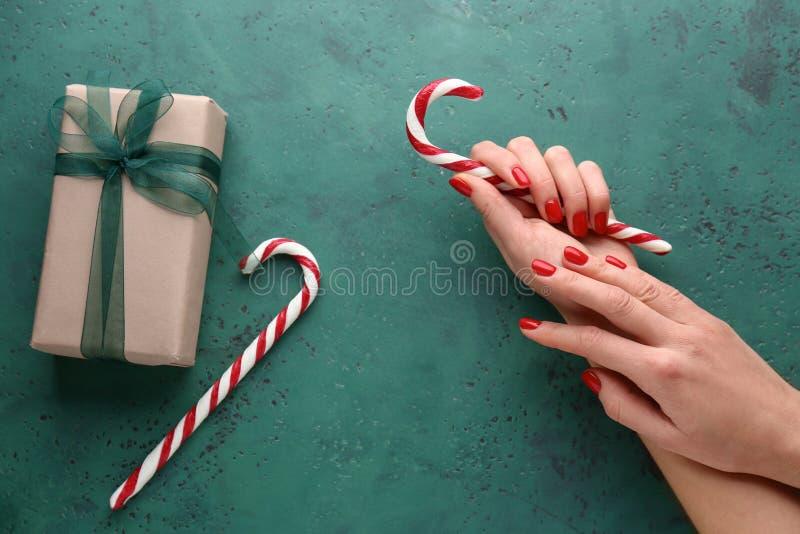 Weibliche Hände mit Zuckerstangen und Geschenkbox auf grünem Hintergrund lizenzfreie stockbilder