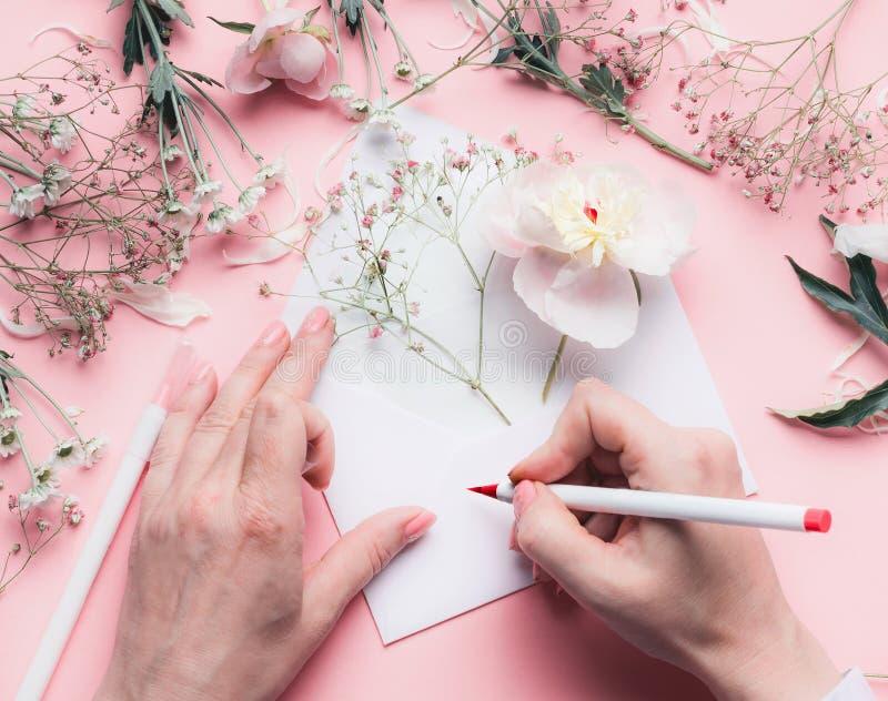 Weibliche Hände schreiben auf Umschlag mit Blumen auf Rosatabellenhintergrund Hochzeit, Einladung, Valentinstag, Mutter-Tagesgruß lizenzfreie stockbilder