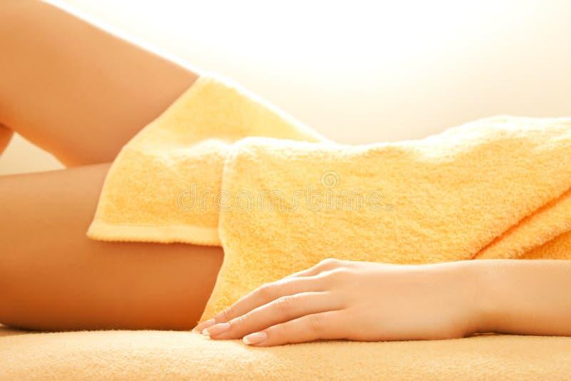 Weibliche Hände und Fahrwerkbeine im Badekurortsalon stockbild