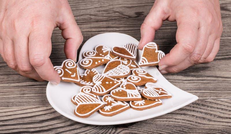 Weibliche Hände und Vorbereitung von süßen Lebkuchen für gutes Glück stockbilder