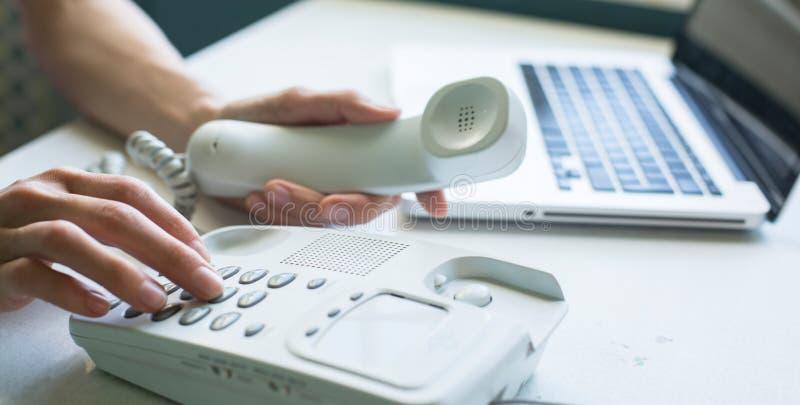 Weibliche Hände unter Verwendung des Telefons, Laptop am Hintergrund büro stockfotografie