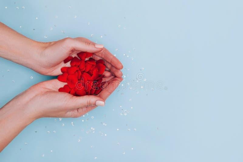Weibliche Hände voll kleiner roter Herzen auf blauem Hintergrund Liebe, Fürsorge, Zuneigung, das Tageskonzept des Valentins stockfotografie