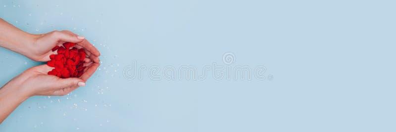 Weibliche Hände voll kleiner roter Herzen auf blauem Hintergrund Liebe, Fürsorge, Zuneigung, das Tageskonzept des Valentins lizenzfreies stockbild