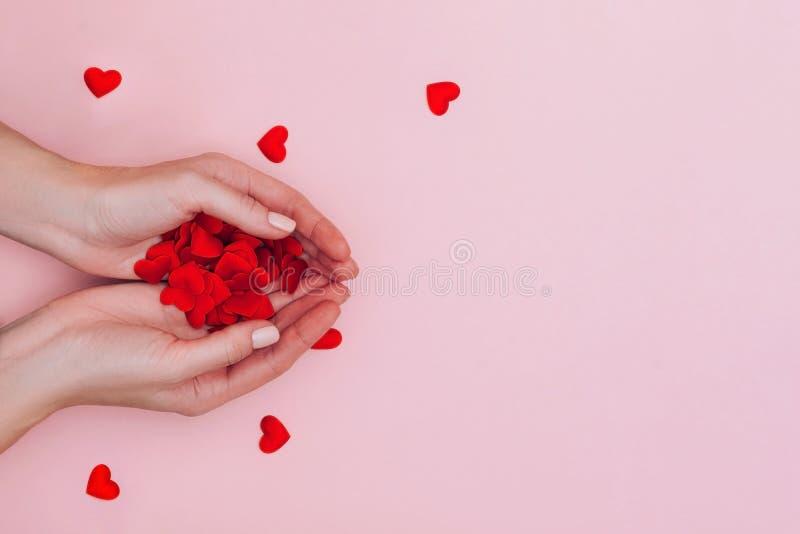 Weibliche Hände voll kleiner roter Herzen auf rosa Untergrund Liebe, Fürsorge, Zuneigung, das Tageskonzept des Valentins stockfotografie