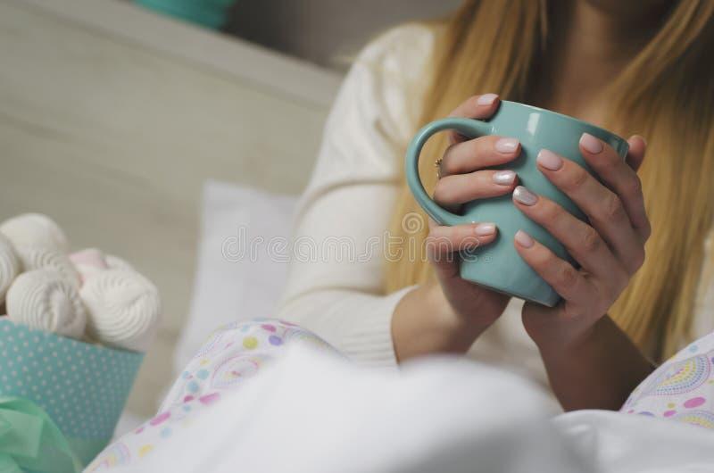 Weibliche H?nde, die einen Becher mit Getr?nk im Bett halten Eibische und Meringen in einem Kasten Gutenmorgen und Entspannungsko lizenzfreies stockbild