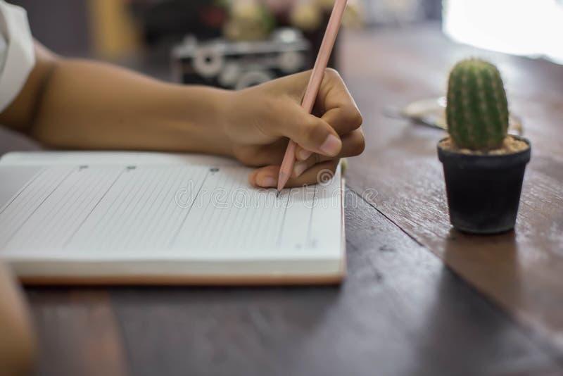 Weibliche H?nde mit Stiftschreiben auf Notizbuch stockfotos