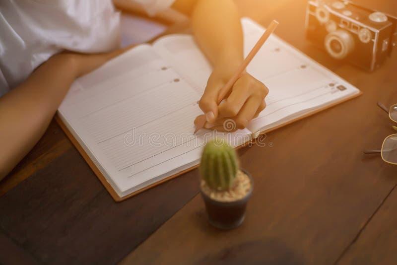 Weibliche H?nde mit Stiftschreiben auf Notizbuch lizenzfreies stockbild
