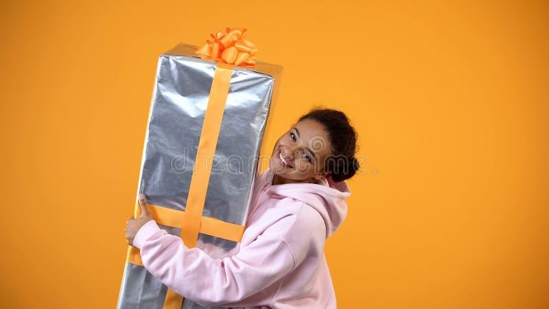 Weibliche haltene betr?chtliche Geschenkbox des gl?cklichen Afrikaners in den H?nden, Feiertagspaket, Verkauf lizenzfreies stockbild