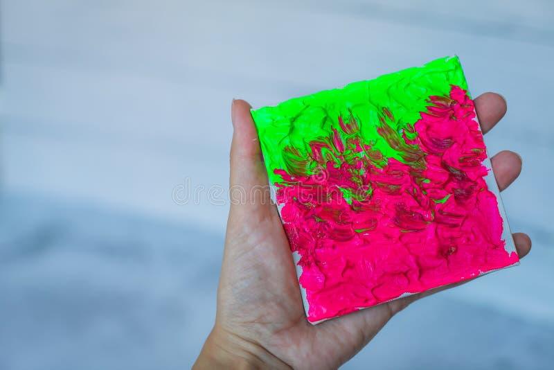 Weibliche Hand der Nahaufnahme mit kreative Kunsthand gezeichneter Acrylmalerei Acrylfarbe der bunten Beschaffenheit der Pinselst stockbild