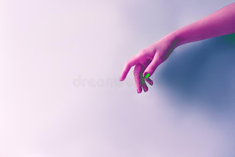Weibliche Hand in der sauren purpurroten Neonfarbe, Minimalismus lizenzfreie stockfotos
