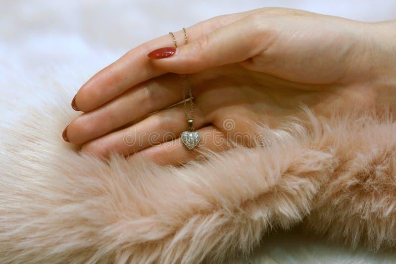Weibliche Hand, die antiken Diamantherzanhänger auf staubigem rosafarbenem Pelz hält stockbild