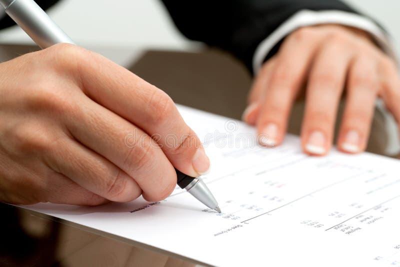 Weibliche Hand, die auf Buchhaltungdokument zeigt. lizenzfreie stockfotos
