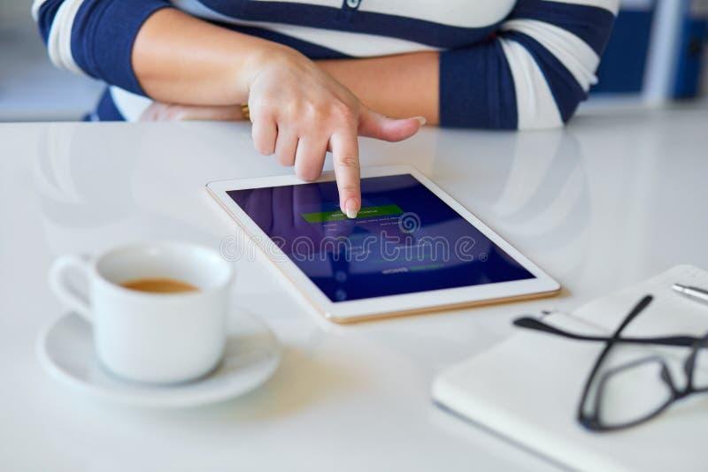 Weibliche Hand, die auf einer Tablette am on-line-Einkaufen sich berührt stockfotografie