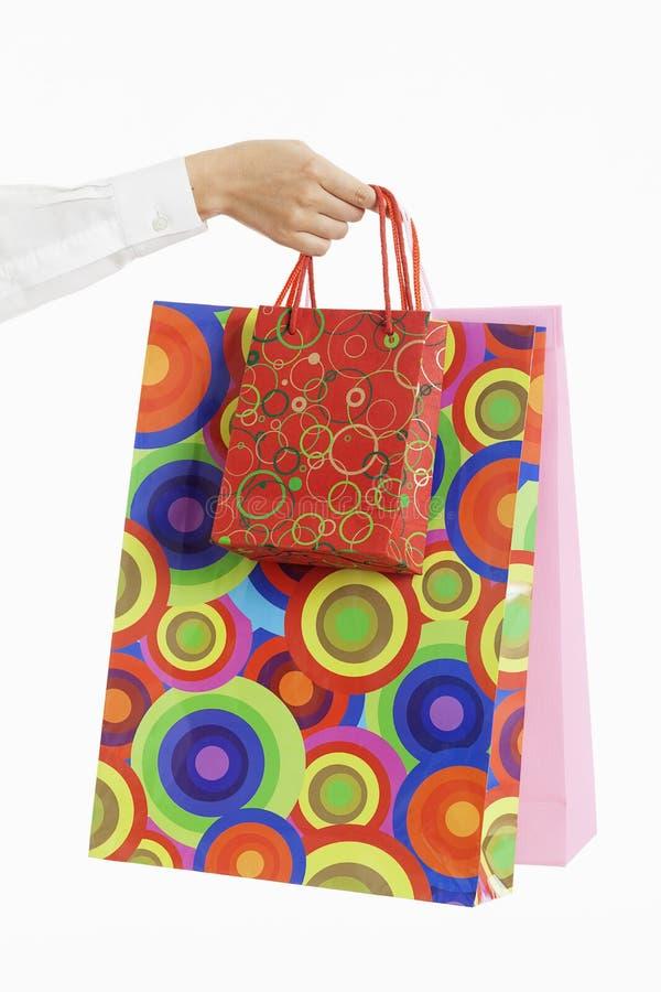 Weibliche Hand, die bunte Einkaufenbeutel anhält stockbilder
