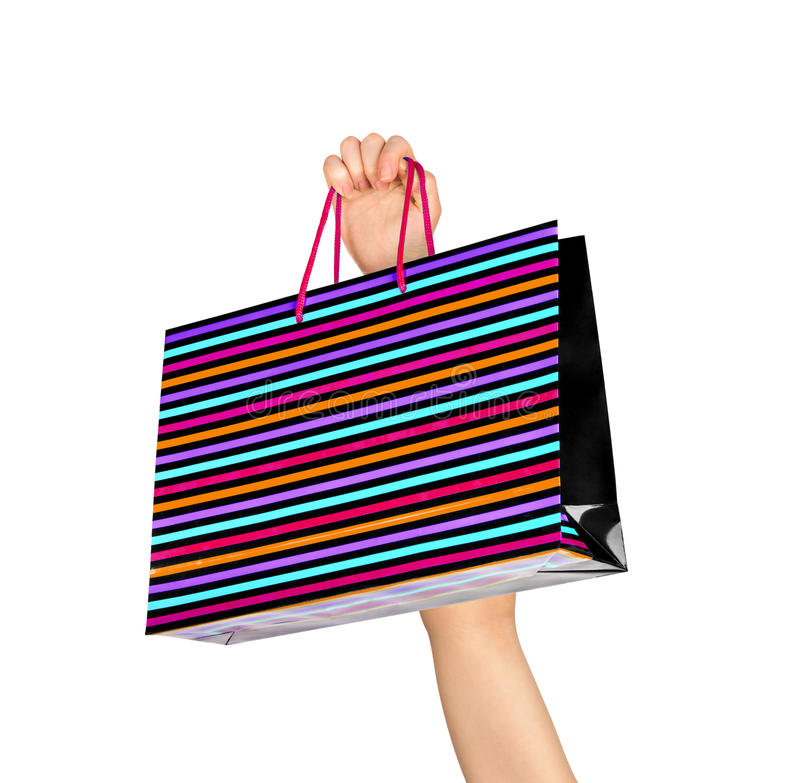 Weibliche Hand, die bunte Einkaufenbeutel anhält stockfotografie