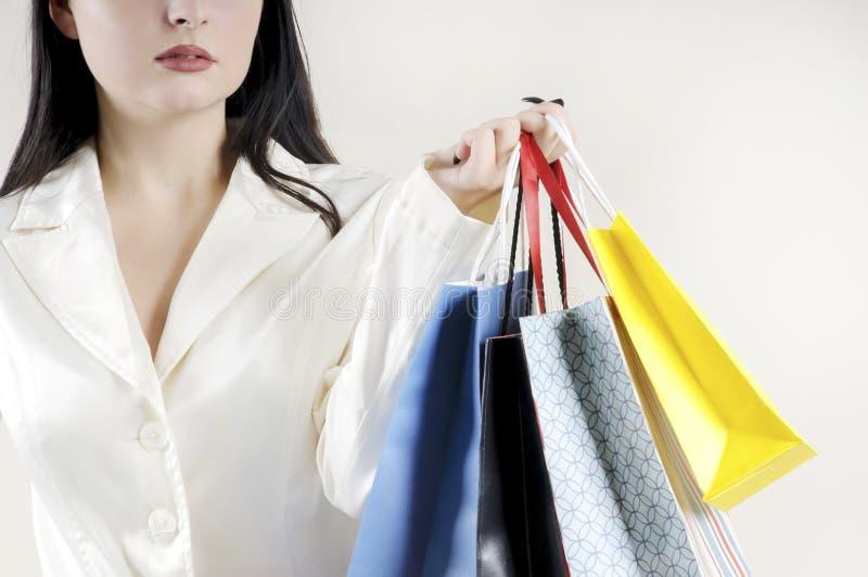 Weibliche Hand, die bunte Einkaufstaschen stilvoll hält lizenzfreie stockbilder