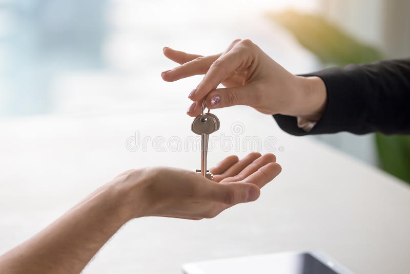 Weibliche Hand, die dem männlichen Kunden Schlüssel, kaufend gibt, Wohnung mietend stockfotos