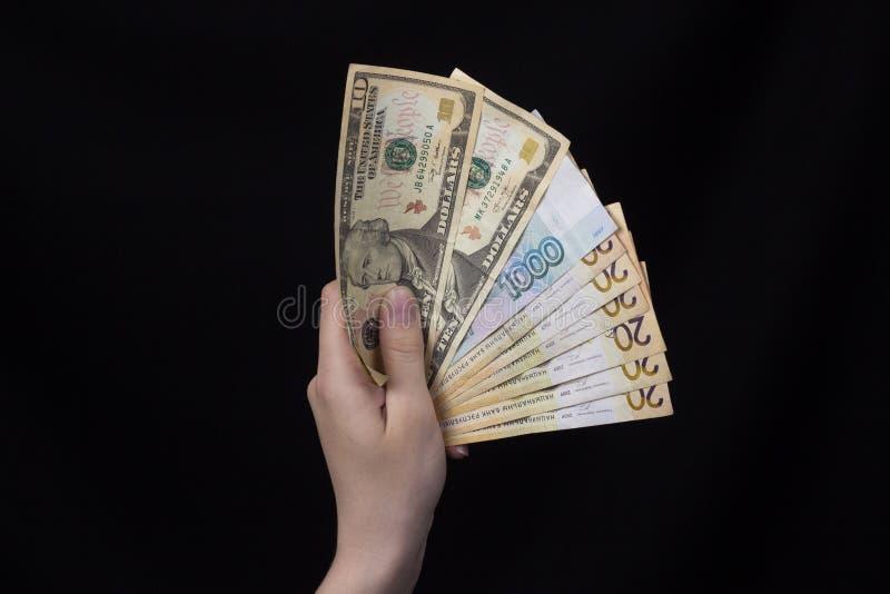 Weibliche Hand, die ein Bündel russische Rubel und Euros der Gelddollar auf einem schwarzen Hintergrund, Nahaufnahme hält stockfoto