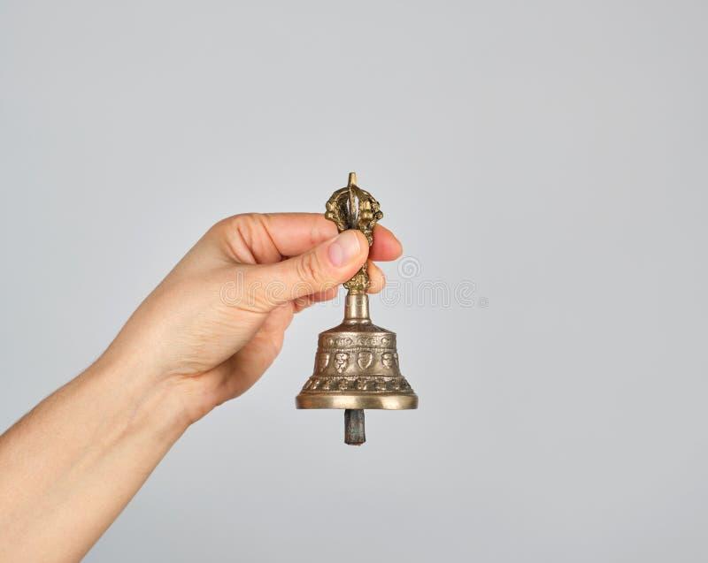 weibliche Hand, die eine Bronzeglocke für Alternativmedizin hält stockbild