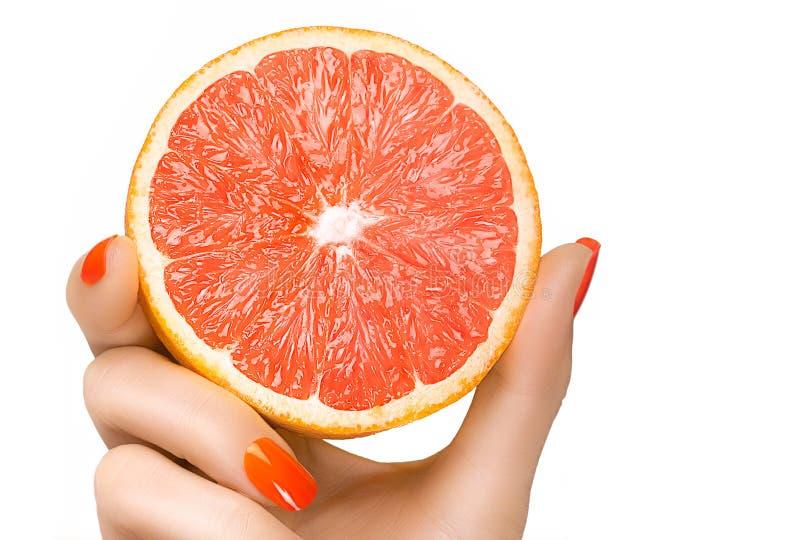 Weibliche Hand, die eine köstliche gesunde Pampelmuse hält Getrennt lizenzfreies stockbild