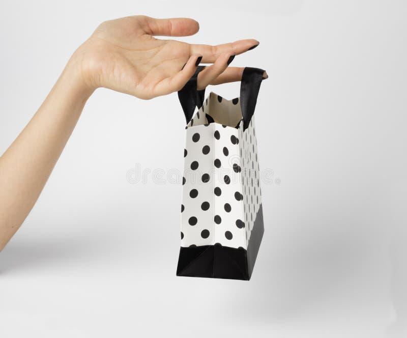 Weibliche Hand, die eine weiße Geschenktasche, mit weißen Tupfen auf ihr hält stockbilder